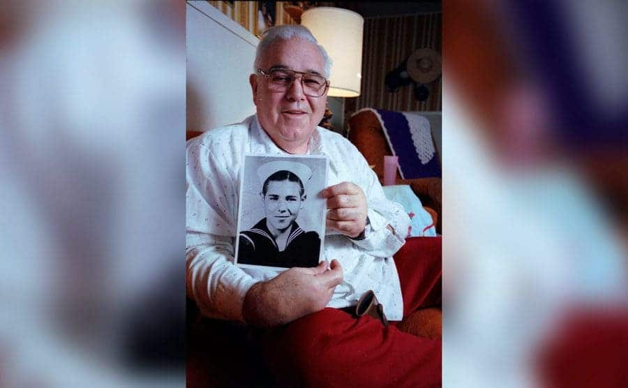 An old age Calvin Graham holding an old black and white photo of himself in the military.