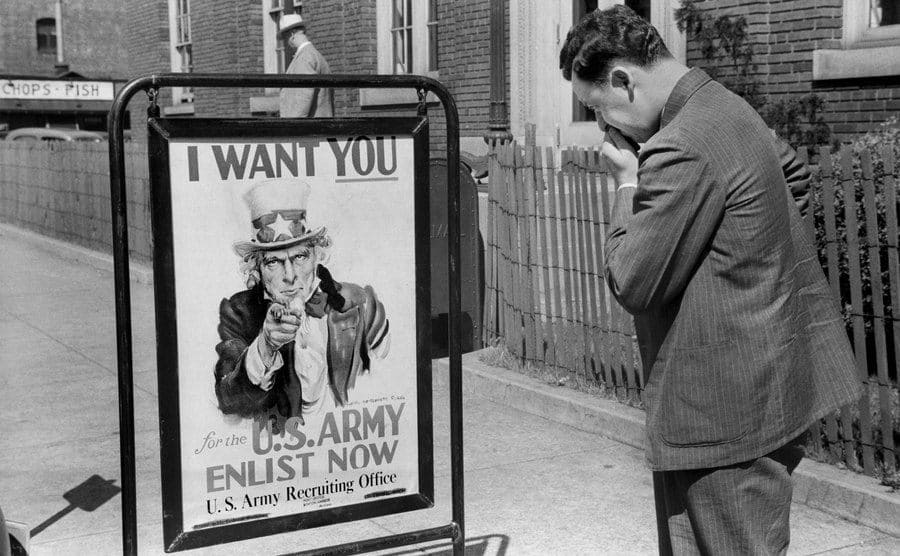 Man Looking at U.S. Army Recruitment Sign on the street.