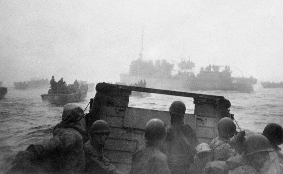 1940s United States Navy landing craft ramp boats fill the water as invasion force soldiers make for shore.