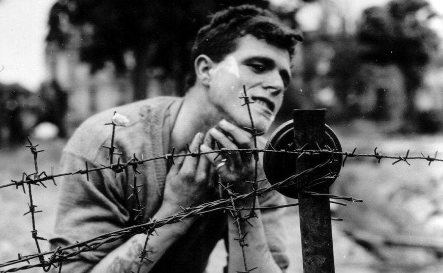 A soldier shaving his beard in a small mirror hanging off a barbed wire fence.