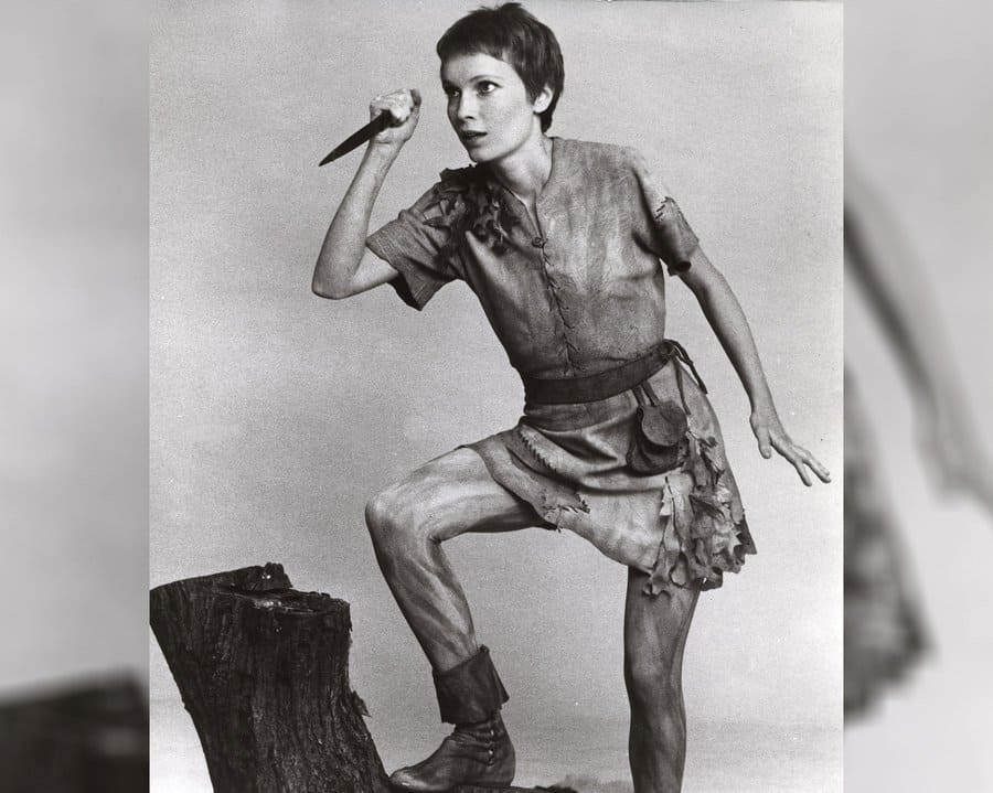 Mia Farrow as Peter Pan holding a knife as if he was about to stab something.