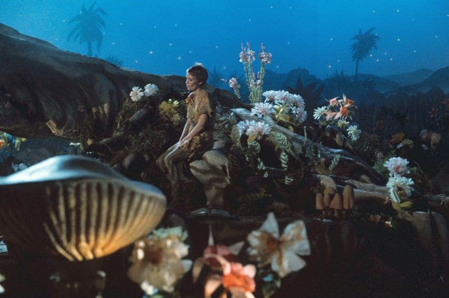 Mia Farrow as Peter Pan in 1976 sitting in the woods surrounded by flowers at night.