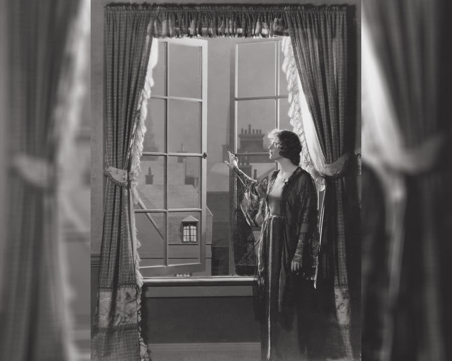 Esther Ralston is looking out of a large open window with long curtains in Peter Pan, 1924.
