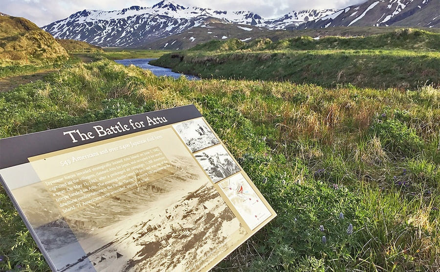 A scene of Attu Island with snow-capped mountains in the background and a grassy field with a sign for the battle of Attu
