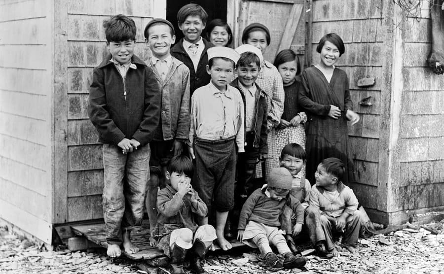 A group of Aleutian children posing in front of a small house