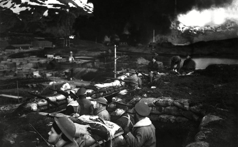 American soldiers sitting around with something burning in the background
