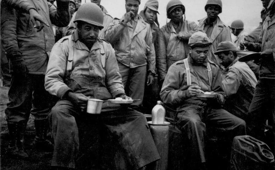 Soldiers standing and sitting enjoying a hot meal in Attu 1943