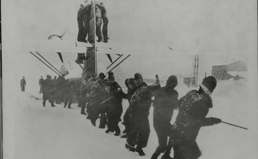 American soldiers on a flying boat to break it out of a snowdrift during a blizzard on the Aleutian Islands