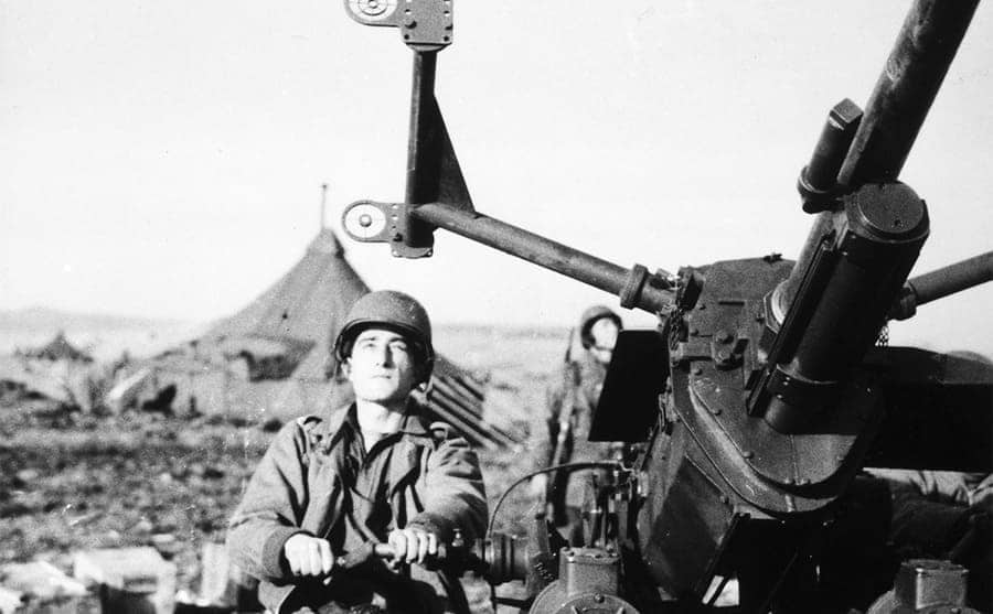 A soldier sitting with a large anti-aircraft gun in a US Army post during the war