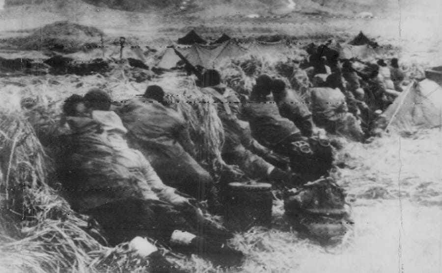 Soldiers crouched down next to a small hill
