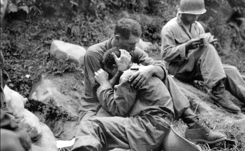 A soldier comforting another soldier who is crying