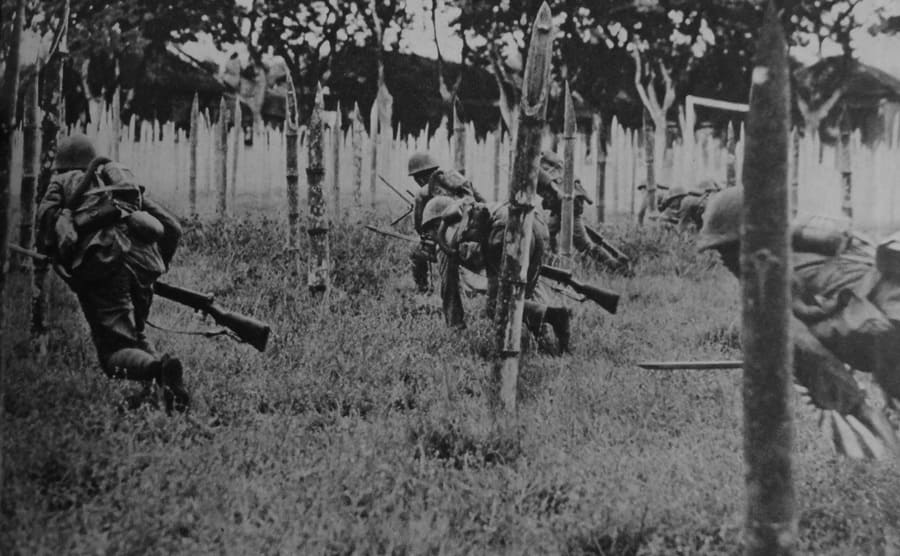 Japanese soldiers advancing through the trees