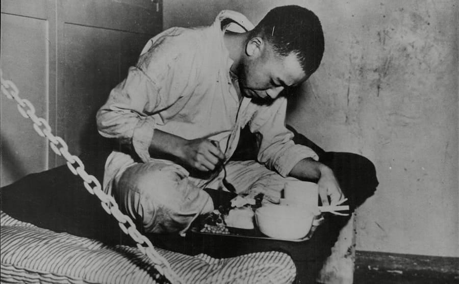 A Japanese prisoner sitting cross-legged enjoying a meal