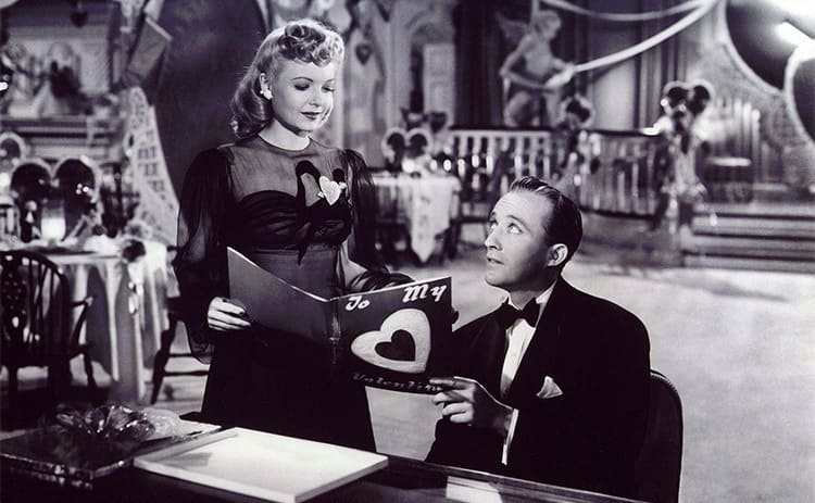 Marjorie Reynolds and Bing Crosby standing by the piano together holding sheet music in Holiday inn 1942