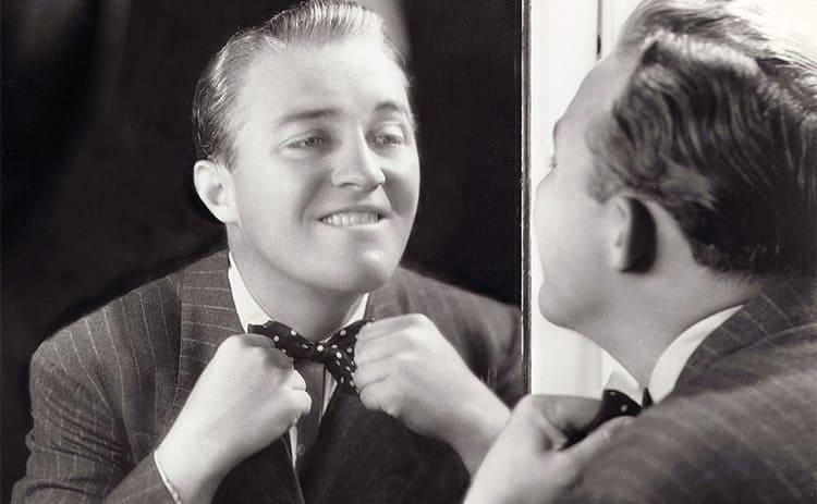 Bing Crosby fixing his bowtie in the mirror circa 1933