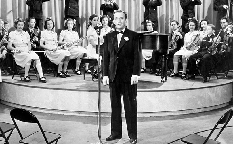 Bing Crosby on stage with an orchestra on stage behind him