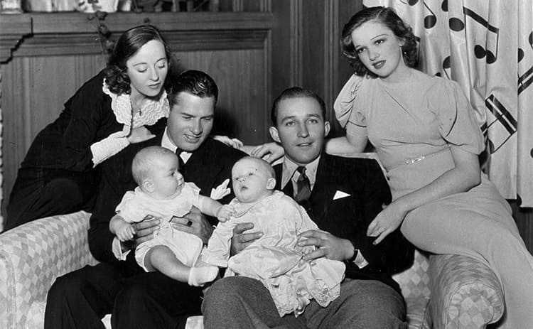 Bing Crosby, Dixie Lee Crosby, and their son sitting together on the couch