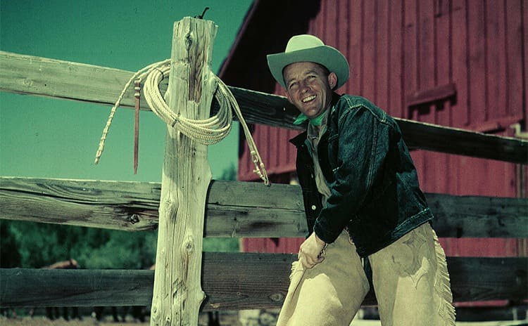 Bing Crosby dressed in a cowboy's outfit in front of a wooden fence