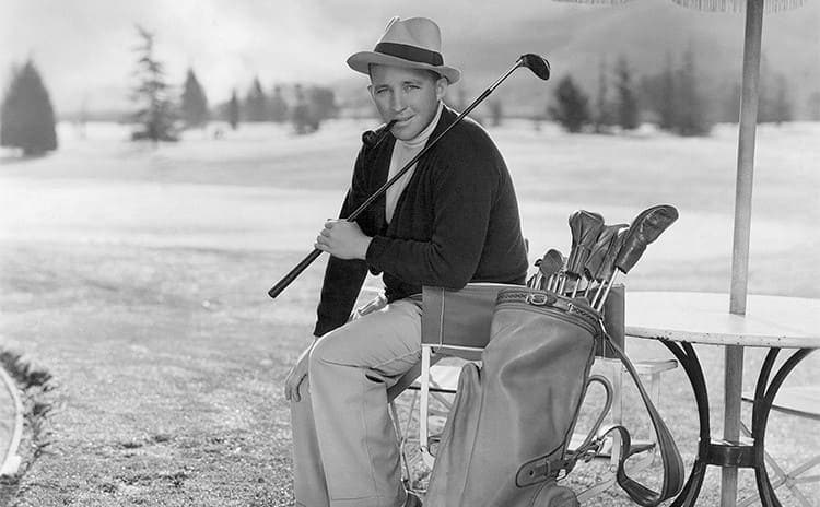 Bing Crosby sitting at an outdoor table holding his golf clubs