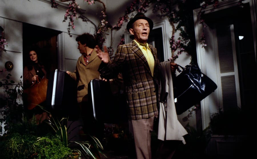Bing Crosby performing on his way out of a house with suitcases on the show Bing Crosby's Merrie Olde Christmas