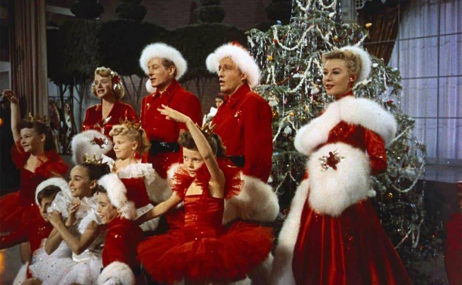 Bing Crosby and others singing in red and white outfits in the film White Christmas