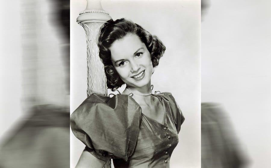 Debbie Reynolds standing against a pole