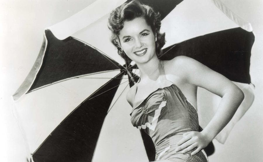Debbie Reynolds posing on top of a lounge chair in the sun with an umbrella over her