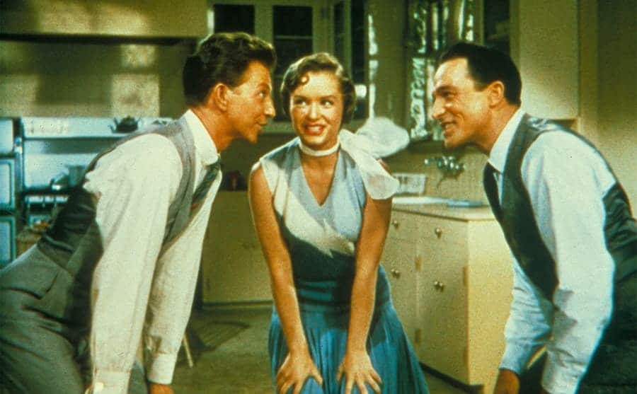 Donald O'Conner, Debbie Reynolds, and Gene Kelly all leaning in and talking in Singing in the Rain