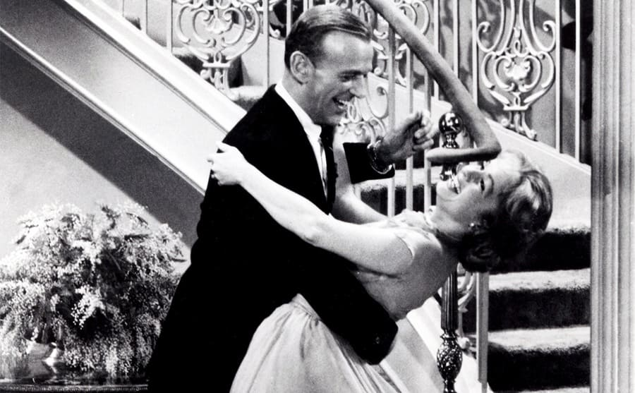 Fred Astaire dipping Debbie Reynolds while dancing near a staircase