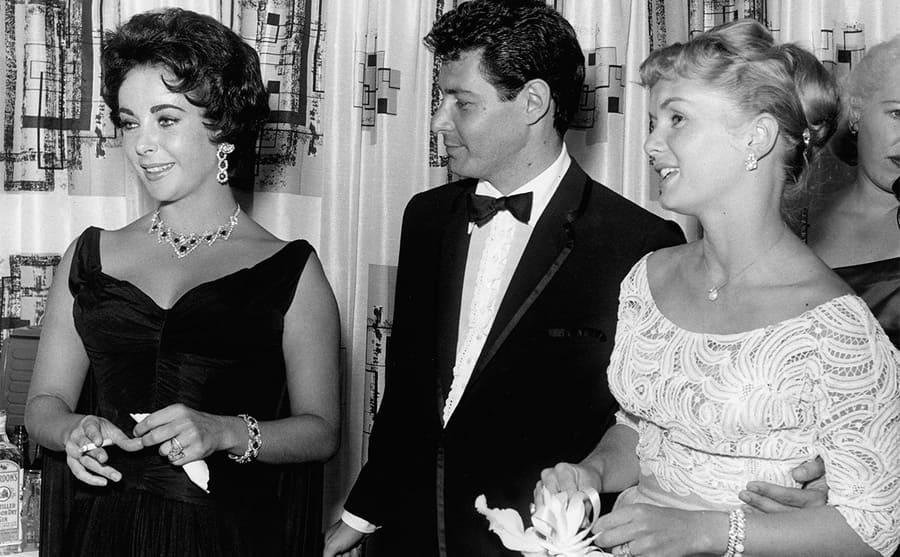 Elizabeth Taylor, Eddie Fisher, and Debbie Reynolds standing together at a party
