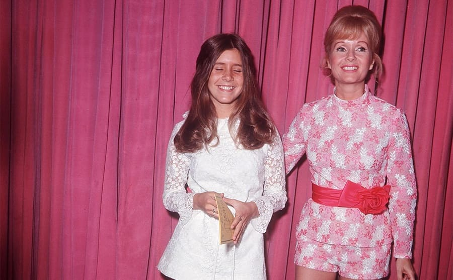Carrie Fisher and Debbie Reynolds dressed up standing in front of a pink curtain circa 1972