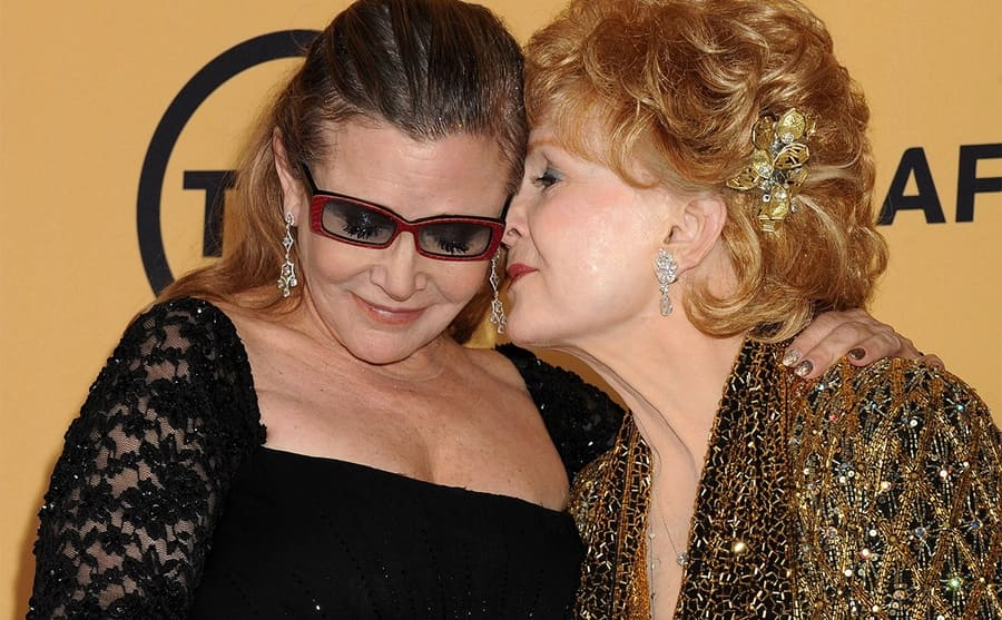 Debbie Reynolds giving Carrie Fisher a kiss on the cheek on the red carpet