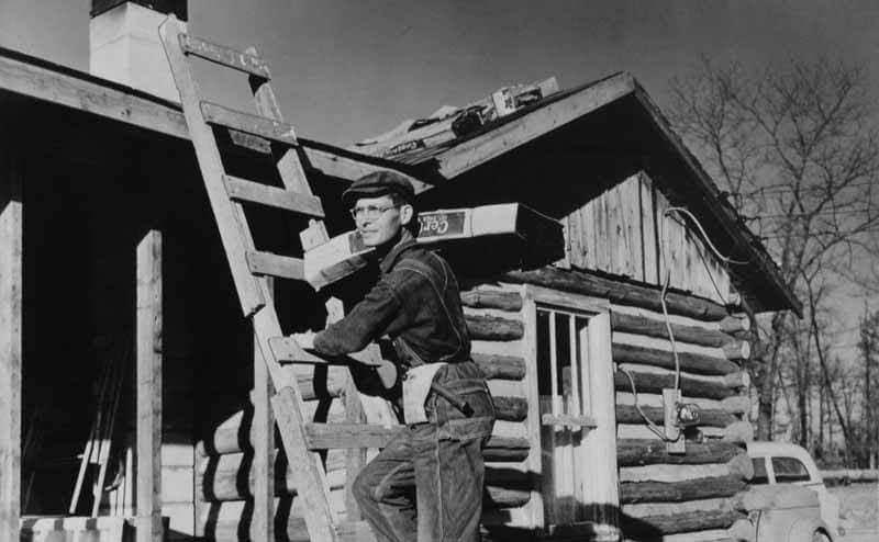 Desmond Doss climbing a ladder on the side of a log cabin