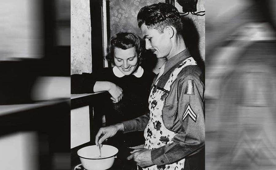Desmond Doss cooking in his uniform with his wife by his side at the stovetop