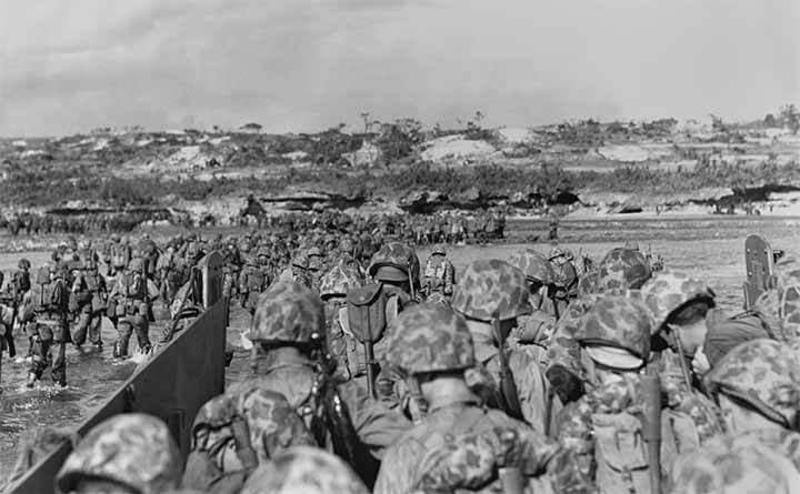 Marines wading over a coral reef to get to the Okinawa beach