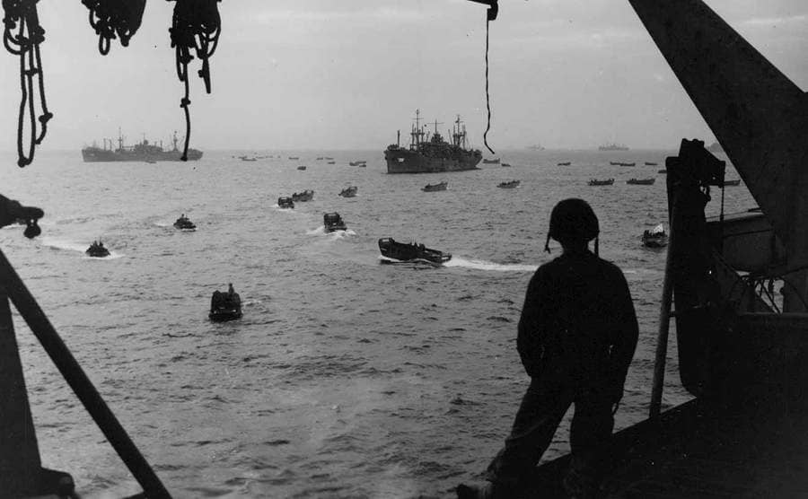 A Marine watching landing crafts off the coast of Okinawa