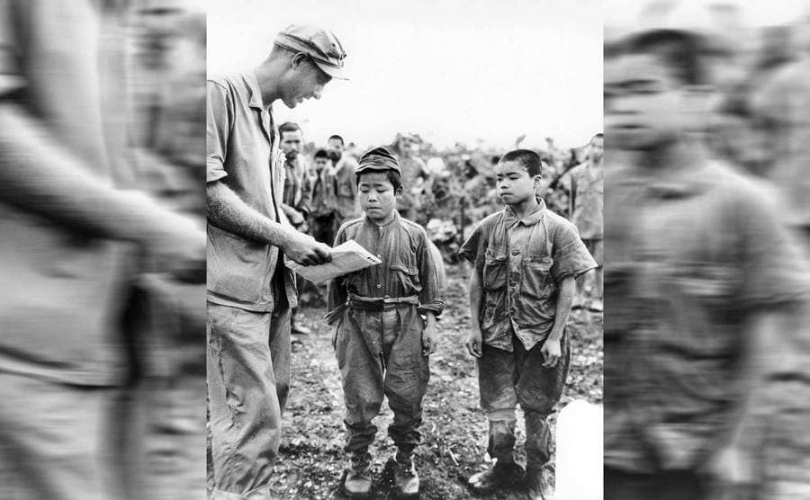 Two Japanese child soldiers standing next to a Marine who is trying to communicate with them circa 1945