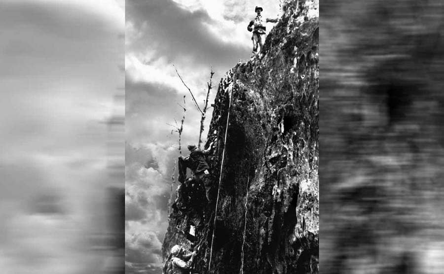Desmond Doss standing at the top of the cliff with soldiers climbing up it