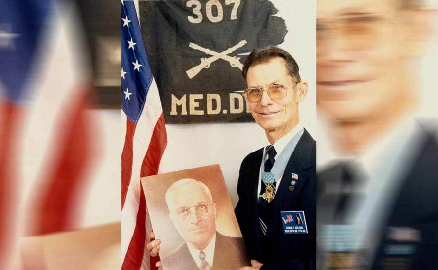 Desmond Doss holding a photograph and posing in his uniform in front of an American flag and an old battalion flag