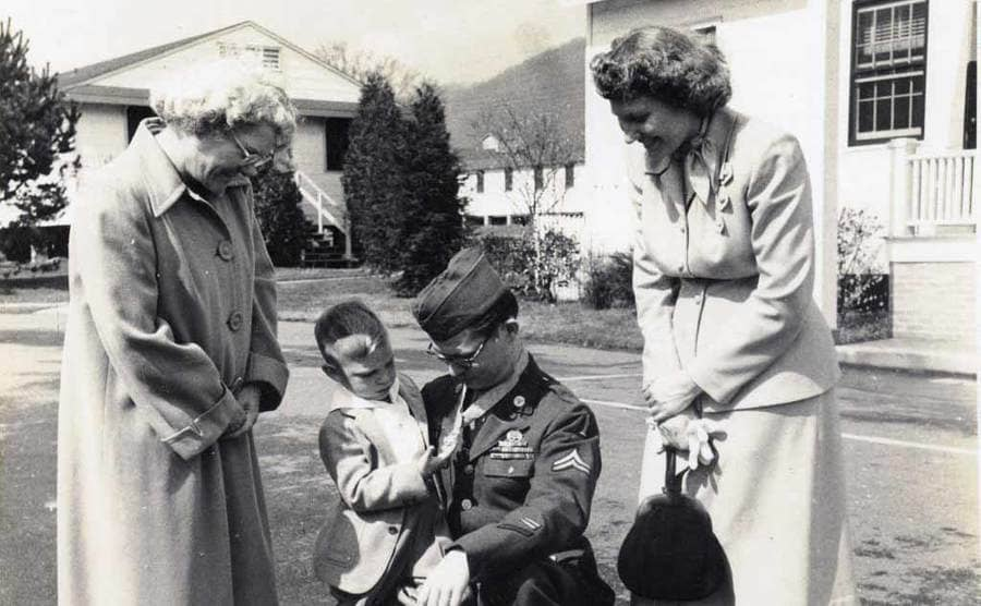 Desmond Doss with his son, who is admiring his medal of honor, and his mother and wife around them