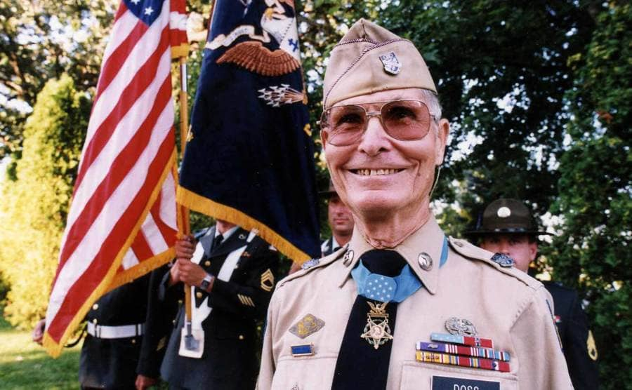 Desmond Doss standing in front of flags and other service men