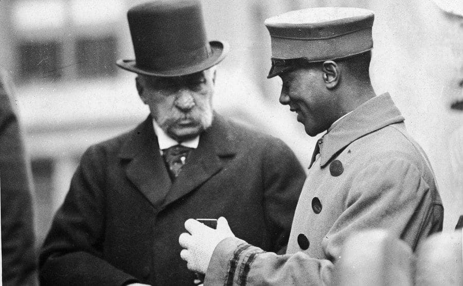 JP Morgan Sr wearing a top hat speaking with a bellboy in the early 1900s