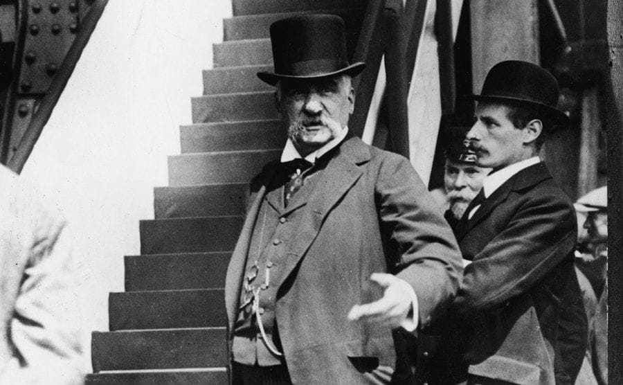 JP Morgan Sr standing at the bottom of a long staircase
