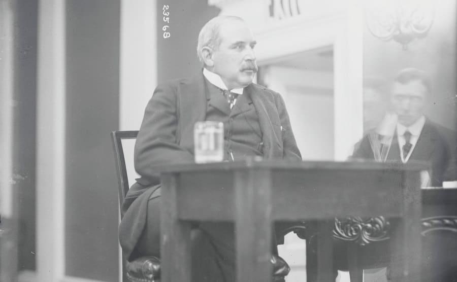 JP Morgan Sr sitting behind a desk