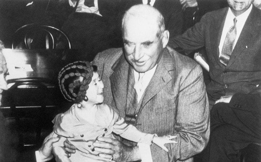 JP Morgan with a little girl sitting on his lap