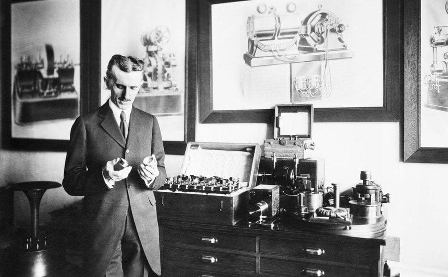 Nikola Tesla holding his coils surrounded by photographs and equipment
