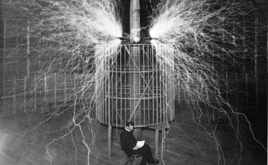 Nikola Tesla sitting in front of coils with electricity sparking from it while he reads a book
