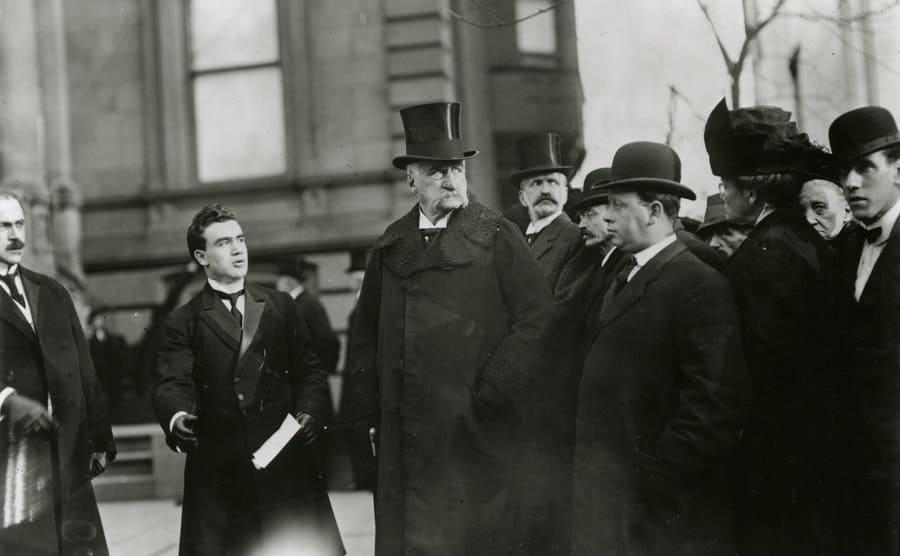JP Morgan walking with a crowd surrounding him