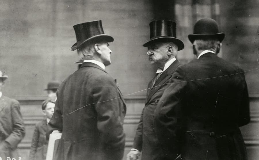 JP Morgan speaking with two businessmen in the street