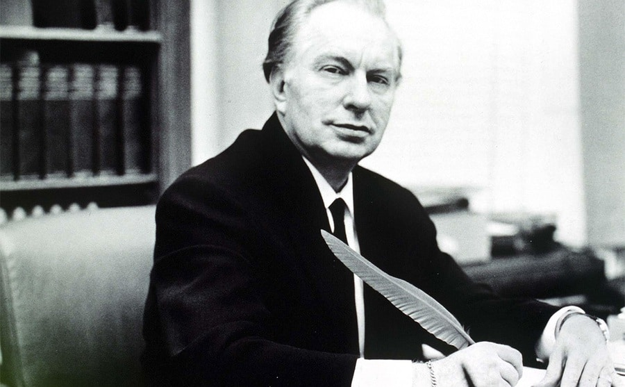 L Ron Hubbard sitting at a desk writing something with a feather